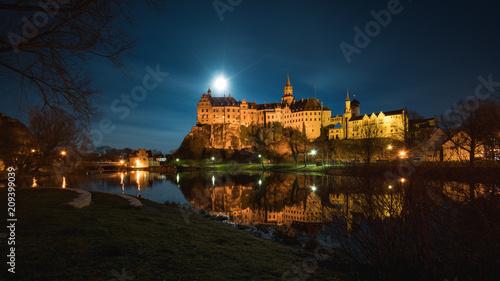 Das Hohenzollernschloss in Sigmaringen liegt direkt an der Donau, der Vollmond neben dem Schloss beleuchtet die Umgebung.