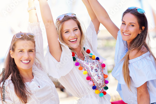 Happy girl friends hanging out in the city in summer - 209399423