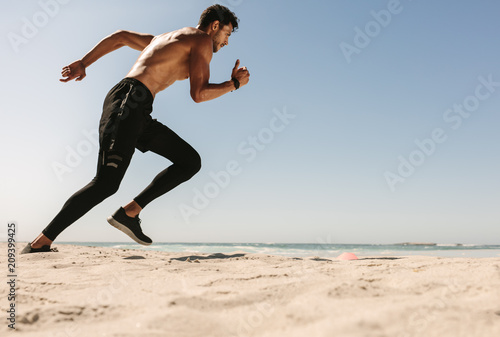 Man running on the beach - 209399425