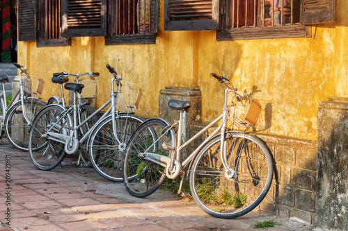 Aluminium Fiets Bicycles parked at yellow wall of old house. Hoi An