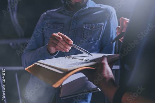 Man in jeans gives advice on work in a notebook with colleagues in office. Low key concept