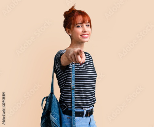 Leinwanddruck Bild Young student redhead girl points finger at you on ocher background