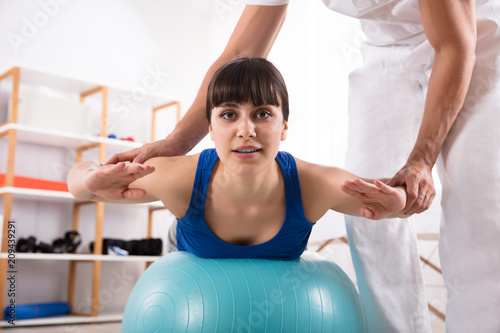 Sticker Physiotherapist Assisting Woman While Doing Exercise