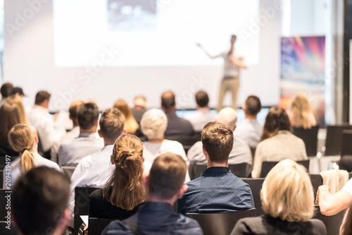 Speaker giving a talk in conference hall at business event. Audience at the conference hall. Business and Entrepreneurship concept. Focus on unrecognizable people in audience. - 209439497