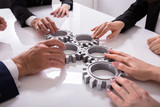 Businesspeople Joining Gears On Desk - 209441234