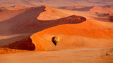 Hot air balloon in flight against orange sand dunes in Sossusvlei Namibia - 209441240