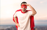 Superhero man with mask and red cape looking far away with hand to look something on a sunset background - 209442432