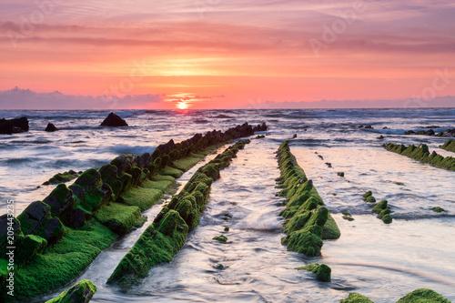 Fotobehang Lichtroze amazing sunset landscape at rocky beach