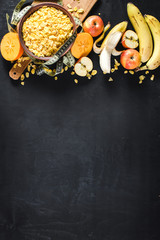 A plate with corn flakes and fruits on black background. Healthy food. Copy space