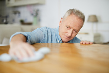 Senior man leaning over table while wiping it with duster during housework