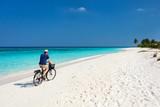 Cycling along tropical beach - 209450660