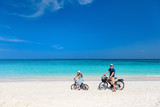 Father and daughter riding bikes at tropical beach - 209450691
