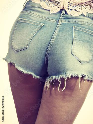 Slim girl wearing denim shorts back view