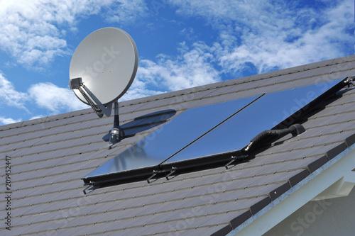 Leinwanddruck Bild Solarthermische Anlage und Sateliten-Anlage auf einem neu gedeckten Ziegeldach montiert