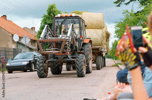 the tractor transports twisted sheaf hay, straw rolls in the trailer of the agricultural machine © NadyZima_klgd