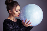 Beautiful young elegant woman holding a moon sphere ornament. Retouched, studio lighting, dark colors and moody feel. - 209460277