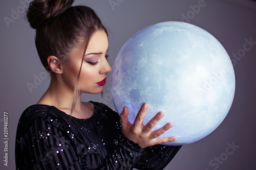 Foto Murales Beautiful young elegant woman holding a moon sphere ornament. Retouched, studio lighting, dark colors and moody feel.