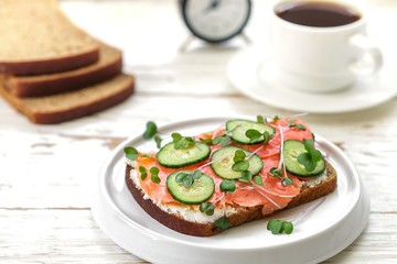 Rye sandwich with salmon, cucumber, cheese cream and micro greens. Tasty and healthy Breakfast on the table.