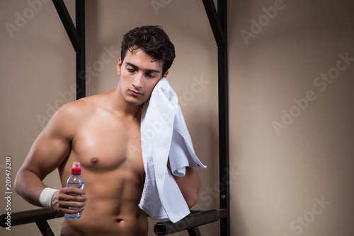 Poster Thirsty man drinking water in sports gym