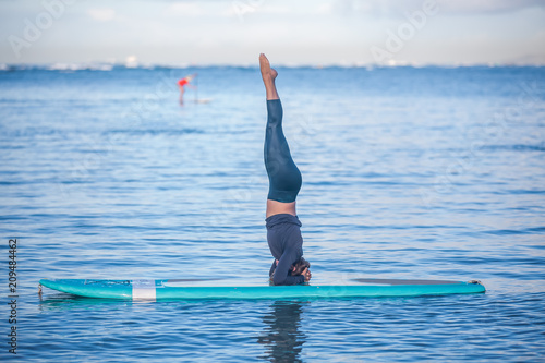Fototapeta Sunny morning work out a pretty young woman in SUP Yoga practice head stand at Ala Moana Hawaii