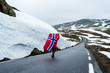 Girl with a Norwegian flag on a mountain road in Norway