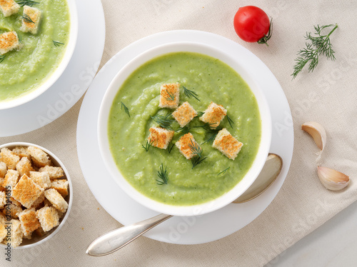 Two large white bowl with vegetable green cream soup of broccoli, zucchini, green peas on white background, top view