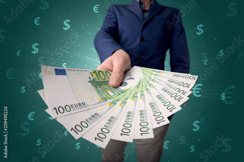 Foto Murales Young businessman holding large amount of bills with green background and currency symbols