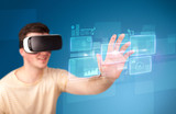 Young impressed man wearing virtual reality goggles with blue squares containing data at his fingers  - 209498645