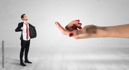 Leinwanddruck Bild Businessman with kisses on his face in an empty space where a big hand baiting him