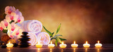 Fototapeta Kwiaty - Spa Concept - Massage Stones With Towels And Candles In Natural Background