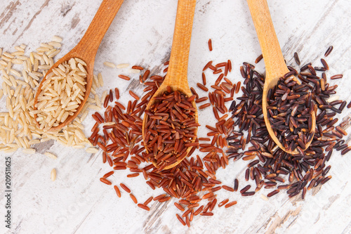 Foto Murales Brown, red and black rice on wooden spoon, healthy nutrition concept