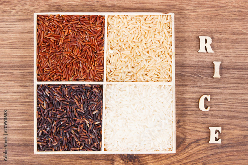 Foto Murales White, brown, black and red rice with inscription on board, healthy gluten free food concept