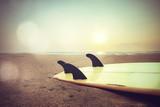 Retro style photo of surfboard on beach at sunset