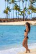 Hawaii beach vacation sexy bikini woman relaxing sunbathing enjoying view of blue ocean at hawaiian travel destination. Asian girl in black swimwear standing on holidays.