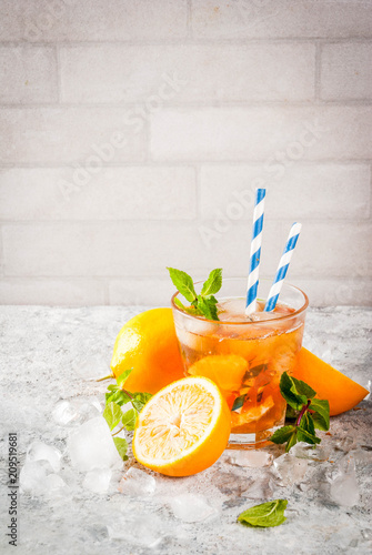 Foto Murales Cold summer drink. iced tea with lemon and mint, on grey stone background.  Copy space