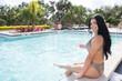 Beautiful hispanic woman swimming at resort