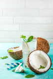 Healthy food concept.  Fresh Organic Coconut Water with coconuts, ice cubes and mint, on light blue background, copy space