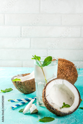 Koncepcja zdrowej żywności. Świeża Organicznie Kokosowa woda z kokosami, kostkami lodu i mennicą, na bławym tle, kopii przestrzeń