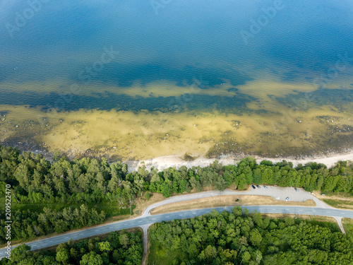 Fotobehang Blauwe jeans drone image. aerial view of Baltic sea shore with rocks and forest on land