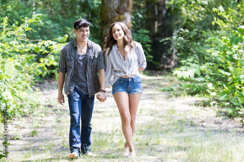 Leinwanddruck Bild Happy young hispanic couple hiking on a trail