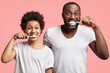 Positve dark skinned son and father brush teeth, keep mouthes wide opened, have satisfied expressions, take care of health, dressed casually, isolated over pink background. Morning routine concept