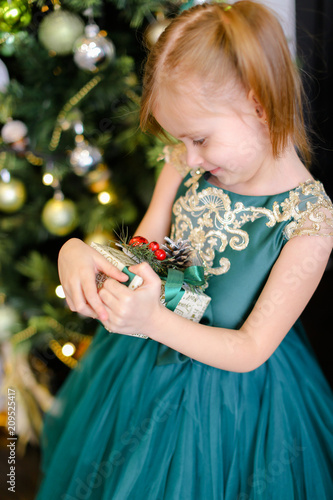 Foto Murales Little pretty girl with gift wearing dress and standing near Christmas tree. Concept of presents, childhood and winter holidays.