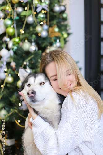 portrait of young blonde girl with husky decorated fir tree in backgroundconcept of