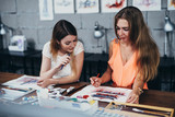 Two adult female students working on their paintings studying at art school - 209533218