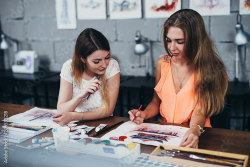 Foto Murales Two adult female students working on their paintings studying at art school