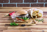 Indian lamb burger with cheese and baked potatoes or chips with red brick wall and wooden worktop background - 209534851