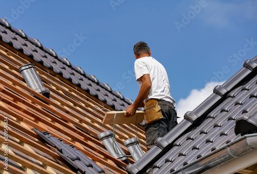 Handwerk - Dachdecker beim Eindecken eines Wohnhauses