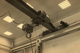 A horizontal crane beam with an electric motor is used to lift and carry heavy objects in an industrial plant  - 209543612