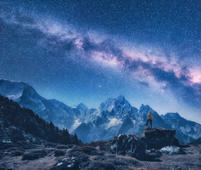 Silhouette of a standing man on the stone, mountains and starry sky with Milky Way at night in Nepal. Sky with stars. Travel. Night landscape with snow-covered mountain ridge and milky way. Space