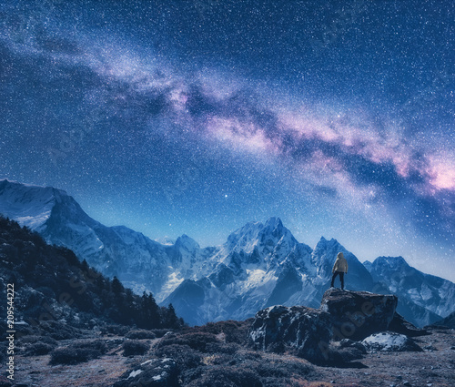 Leinwanddruck Bild Silhouette of a standing man on the stone, mountains and starry sky with Milky Way at night in Nepal. Sky with stars. Travel. Night landscape with snow-covered mountain ridge and milky way. Space